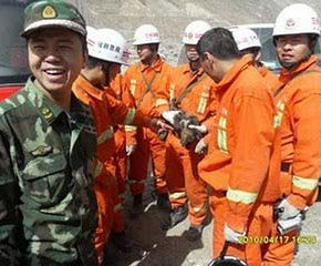 チベタンマスティフの子犬を助け談笑する救助隊員たち