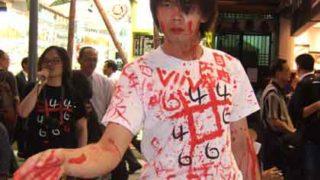 青年の流血の弾圧を告発するパフォーマンス