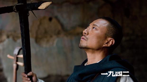 手製の十字架を掲げる安西満 映画『温故1942』より