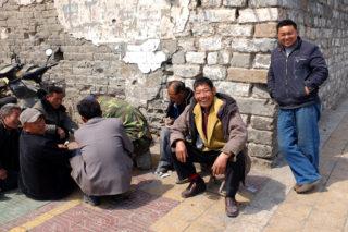 城壁の下でトランプに興じる市民