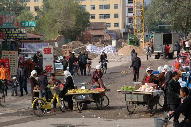 山丹市街。土が露出した空き地で屋台が店を開いている。大きな「鑲牙」(入れ歯)の看板がおもしろい。中国の田舎では、露天の歯医者はめずらしくない