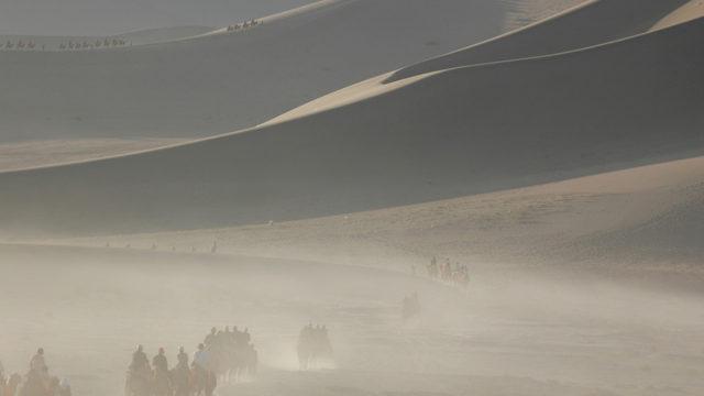 敦煌鳴沙山。朝日をあびて砂山の稜線がくっきりと浮かびあがる。足に鈴をつけた駱駝が1日の活動をはじめる