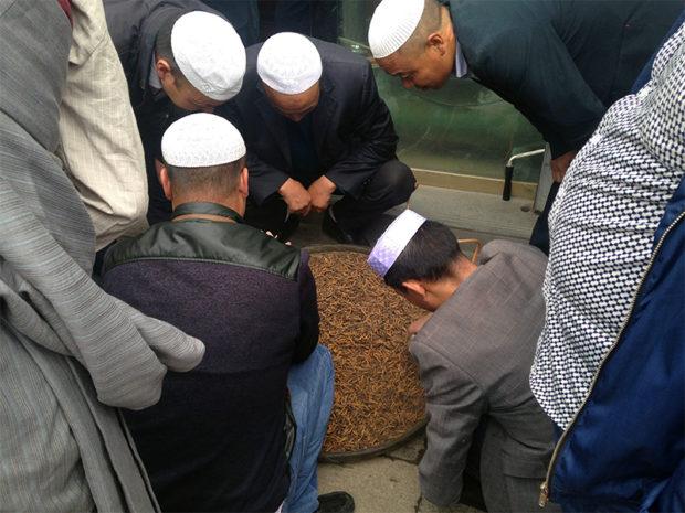 ラサのモスク近くでチベット人が店に持ち込んだ冬虫夏草を見定める回族の商人