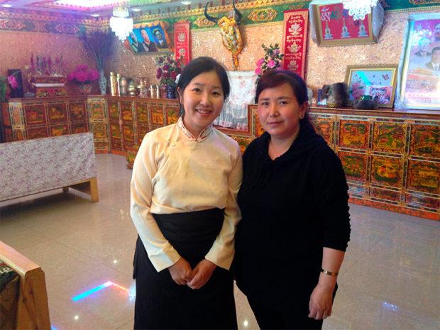 ラサの裕福なチベット人家庭。モナリザの微笑を浮かべる女主人(右)と筆者(左)。背後には「党中央の核心」の写真