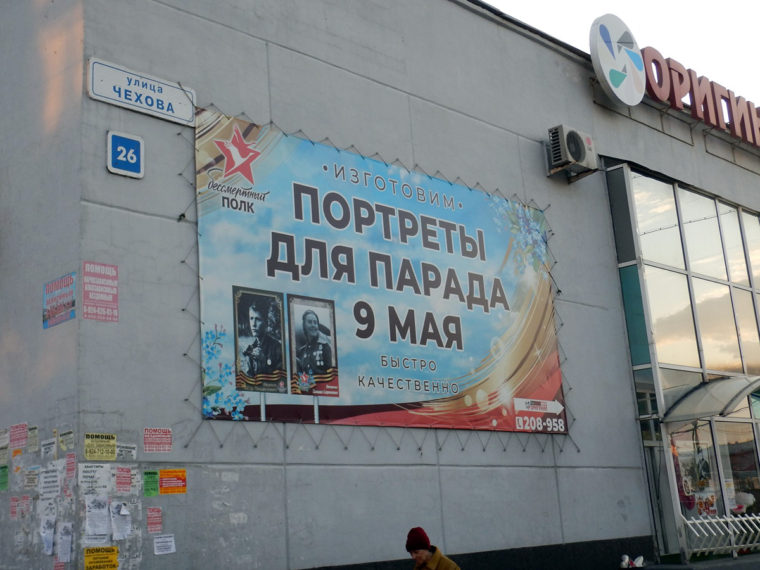 戦勝記念日のパレードで掲げるための肖像画の制作を行う会社の広告。戦勝記念日には、かつて戦争に参加した近親者の肖像画を掲げてパレードをする習慣がある。