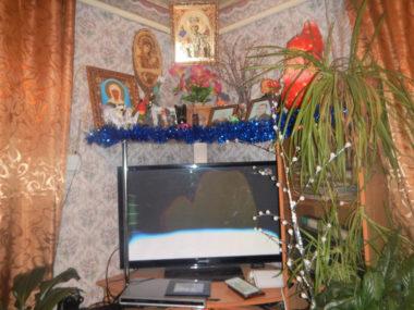 農村のとある家庭の居間。テレビやPCなど、設備面では都市部とほとんど変わらない。上には家族の写真やイコンが飾られている。